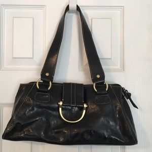 Black shoulder bag with burnished brass accents.